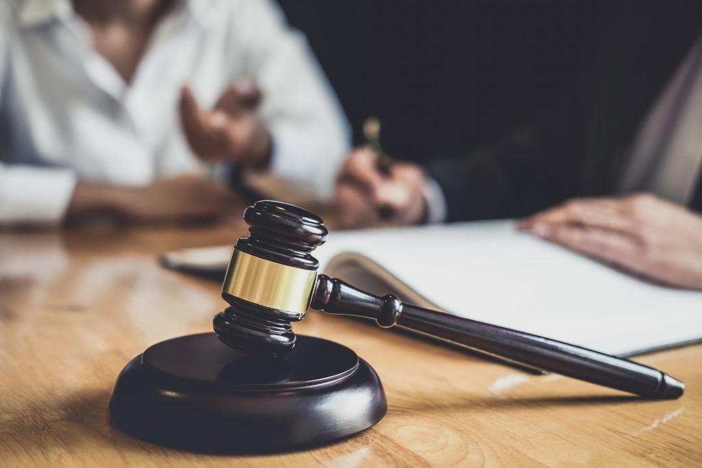 Crime de falsidade ideológica - Advogado conversando com seu cliente. Ambos sentados